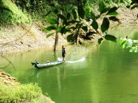 A fisherman uses an entrameling net ion Batang Ai, Sabah. Malaysian Borneo